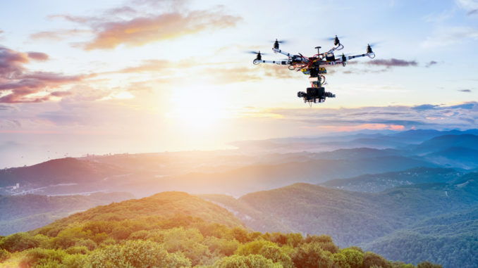 drone flying over mountains with sunset